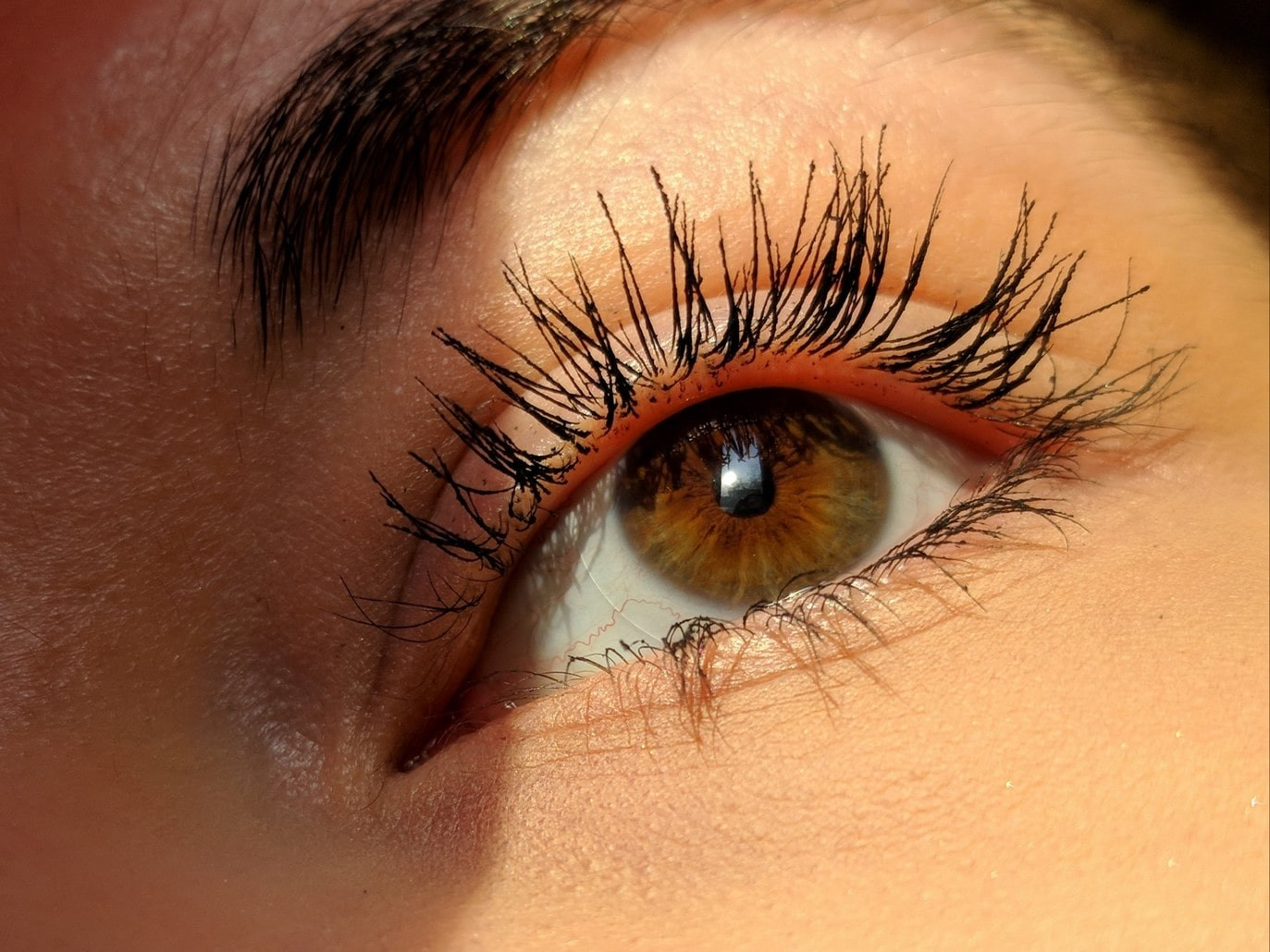 close up of woman's eye area showing her curled eyelashes.