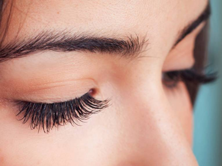 close up on womans eyelash extensions