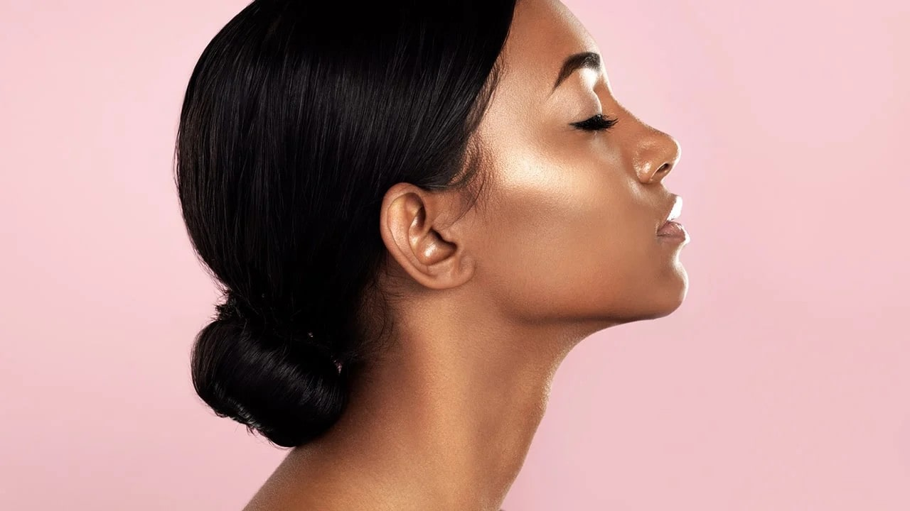 side profile of a woman with glowing skin.