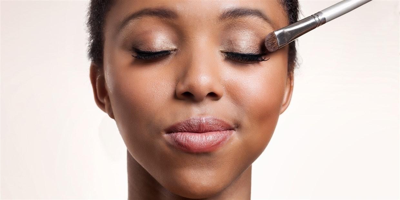 woman applying a light setting powder to her eyelid.