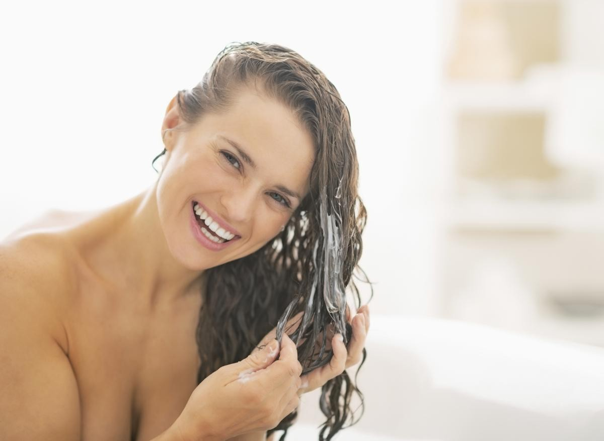 woman conditioning hair, which can be also be an essential element to avoiding brassy hair.