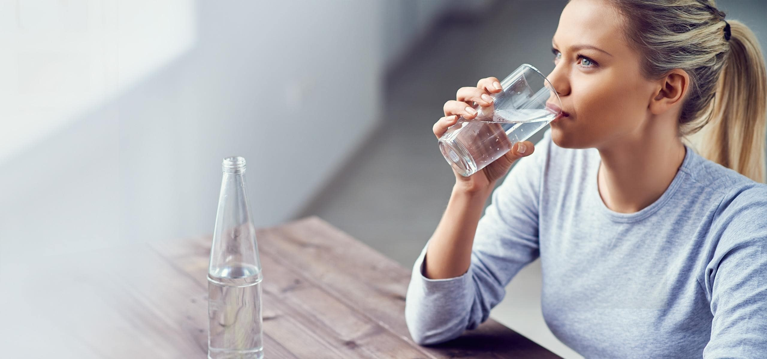 woman drinking water, whilst sat at a wooden table.