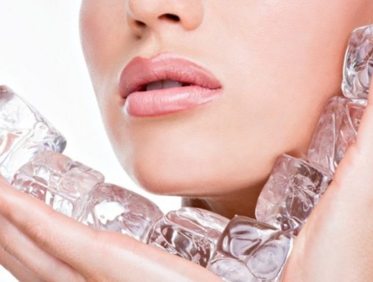 woman holding ice cubes to her skin.