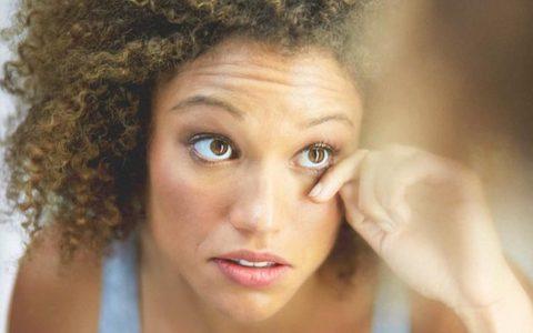 woman touching below her eye.