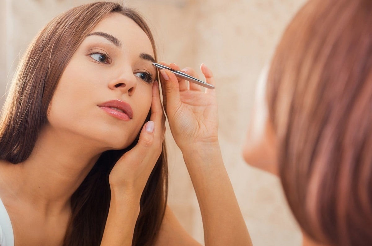 woman tweezing/plucking her eyebrows whilst looking into the mirror.