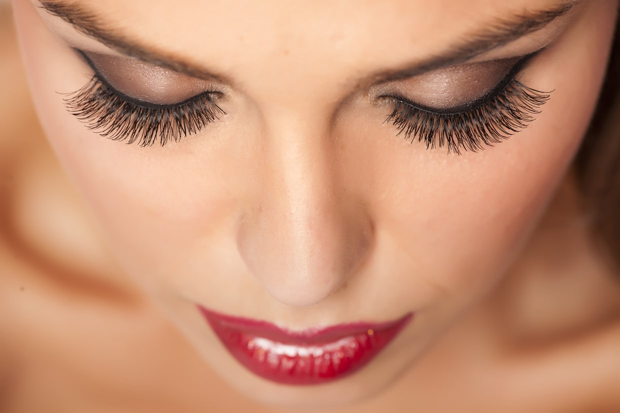 woman with red lips and eye lash extensions.