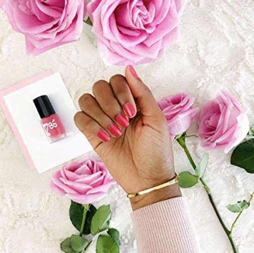 close up of hand, posing with 786 nail polish on and the bottle in the background, with roses and rose petals sprawled below.