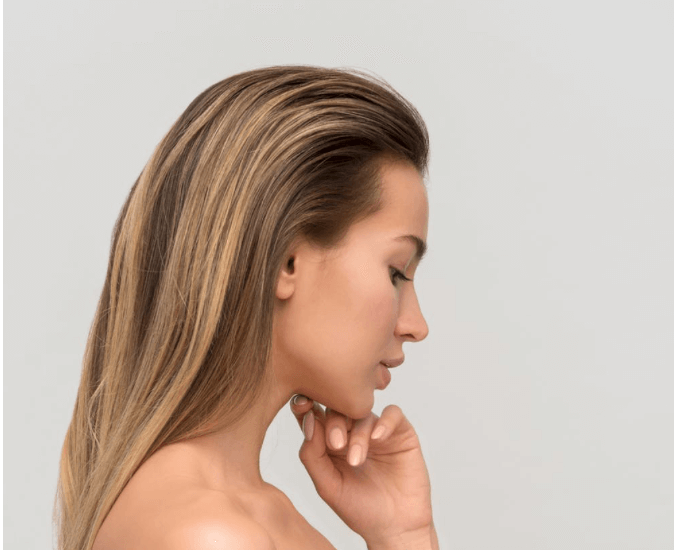 Woman with blonde hair touching her face