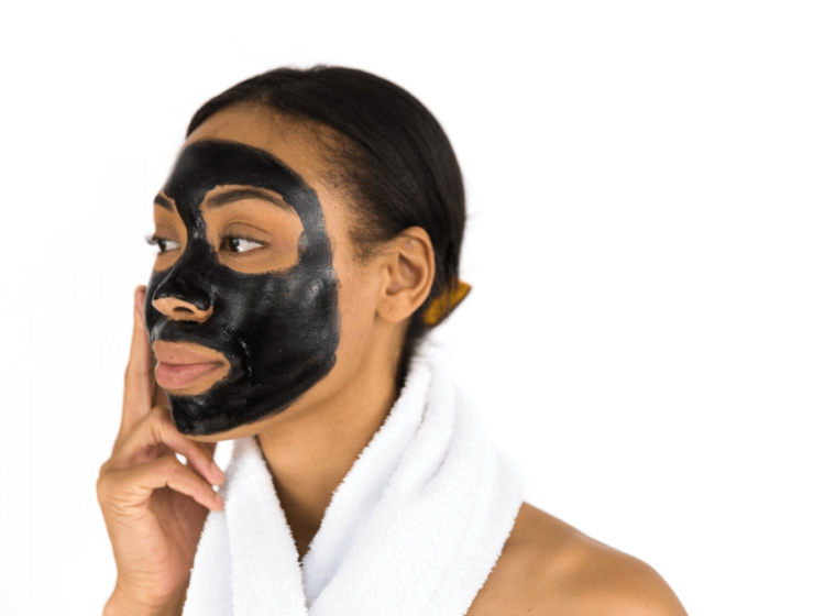 A woman with a black face mask on and towel around her neck