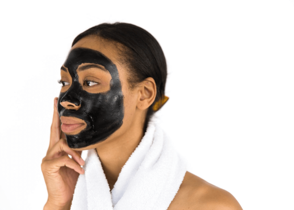 Woman wearing a black face mask with a towel around her neck