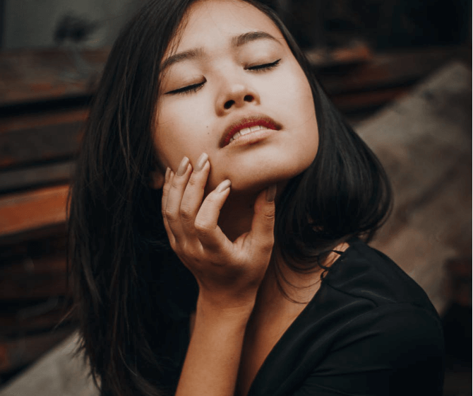 A woman wearing a black dress and touching her face