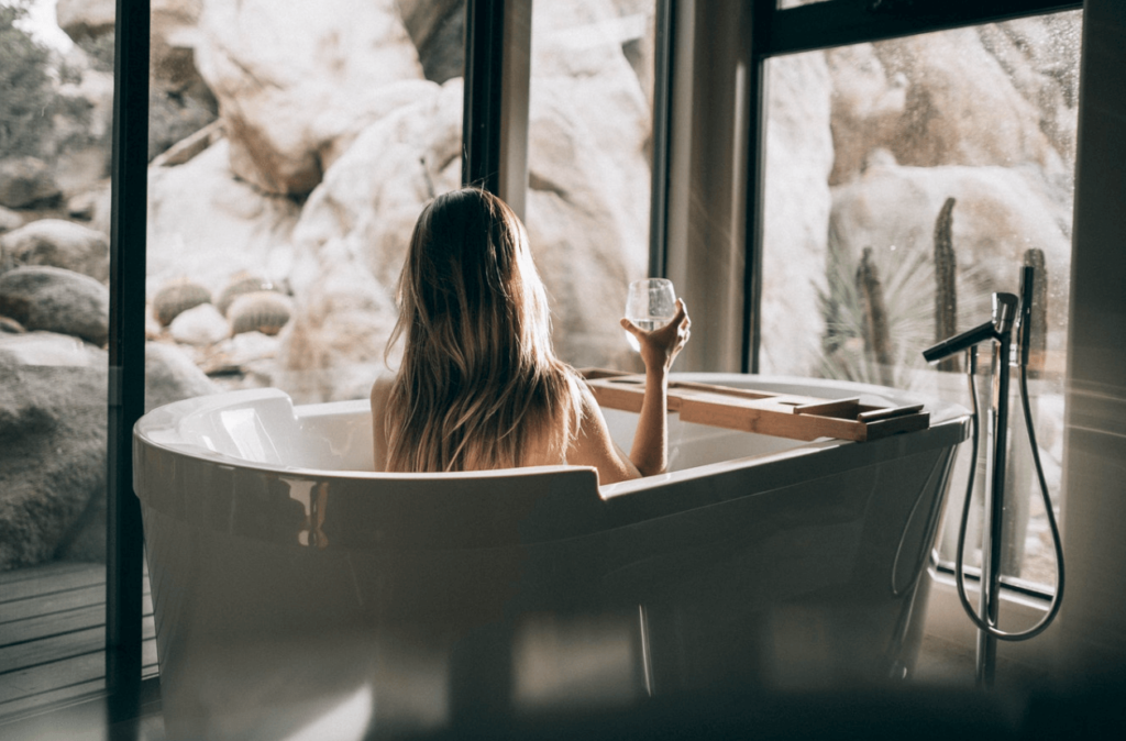 Woman sitting in the bath with a glass of wine