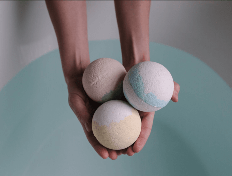Person holding three bath bombs near a bath full of water