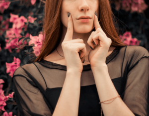 A woman standing near a floral background and touching her face
