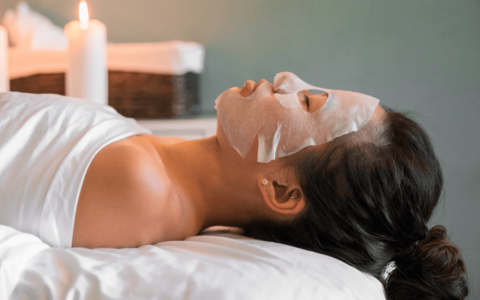 Woman wearing a face mask and getting a facial treatment at a spa