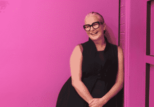 A mature woman standing near a pink wall wearing glasses