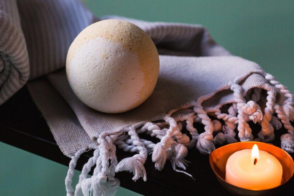 A bath bomb on cloth near a bath with a candle