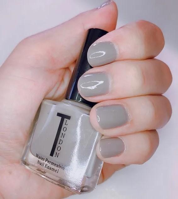 close up of hand, with fingernails wearing taylah london nail polish in a light-grey shade.