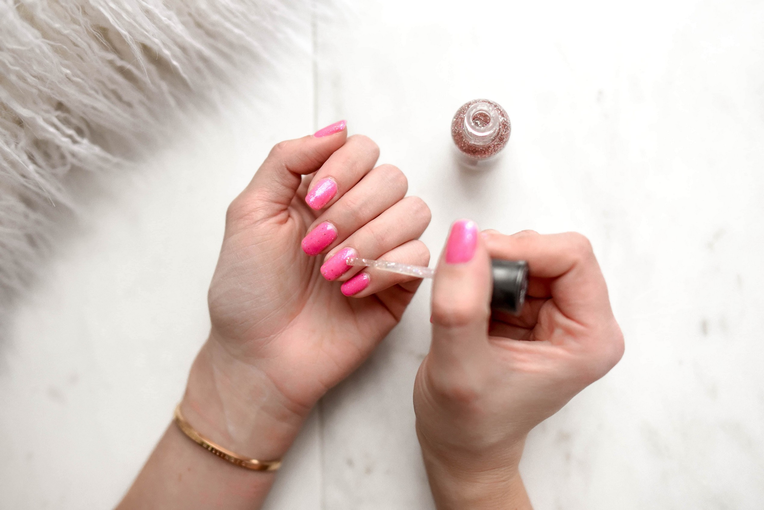 A person applying nail polish, possibly Water-Permeable.