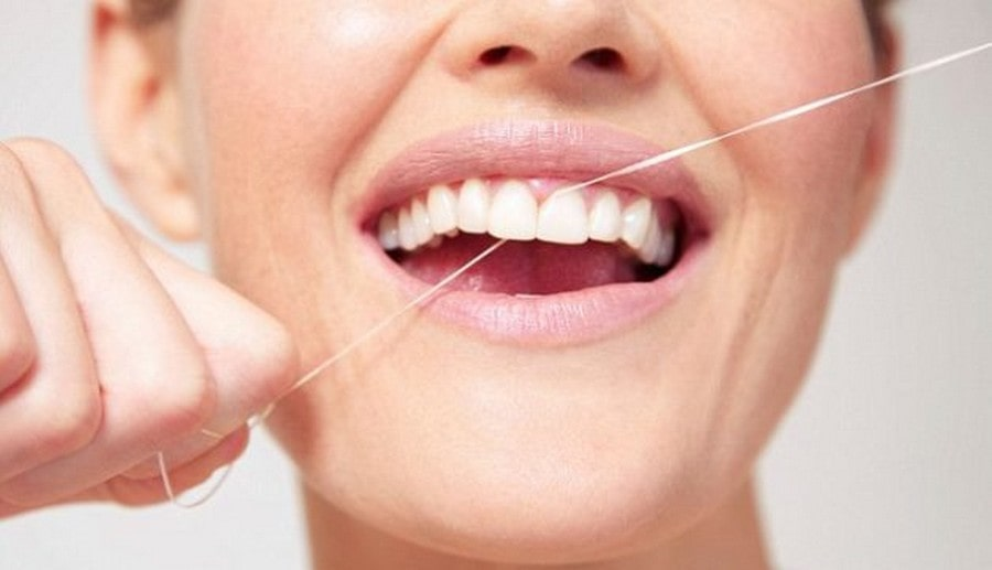 close up of a woman flossing between her teeth.