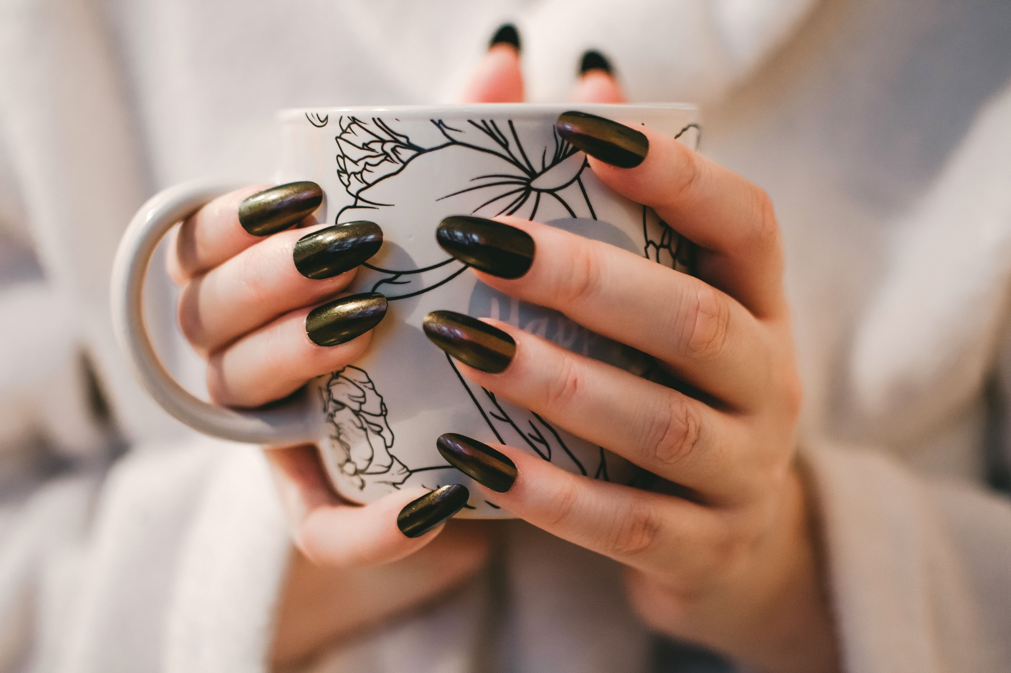close up picture of a woman holding a flower patterned mug whilst wearing black nail polish on her long nails.