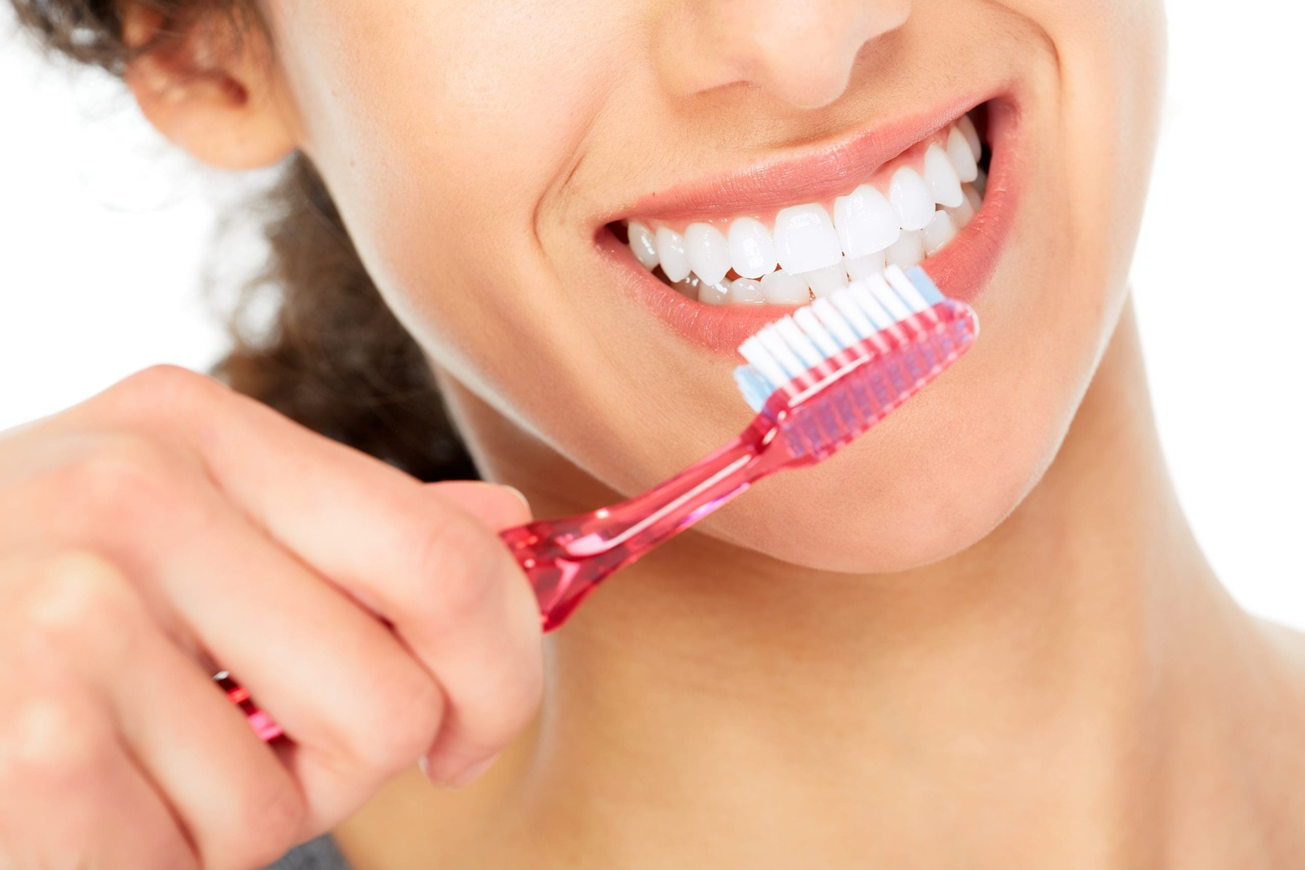 close up of a woman using a toothbrush on her teeth.