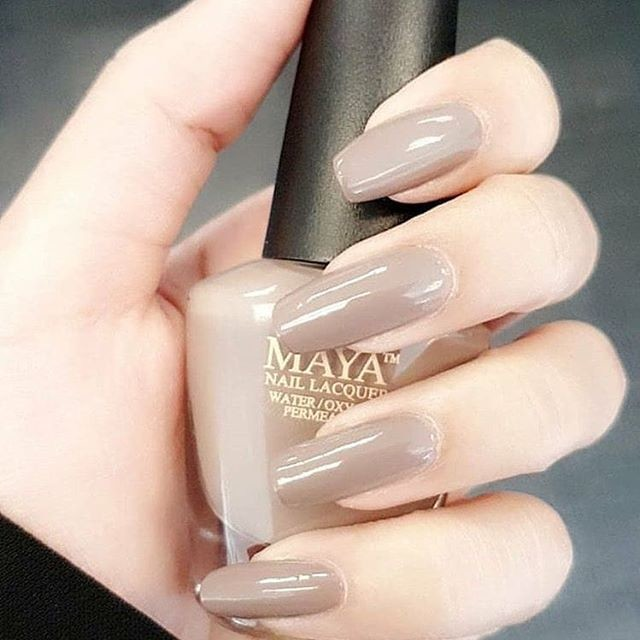 close up of individual holding a bottle of maya nail lacquer, with the nail polish displayed on their nails.