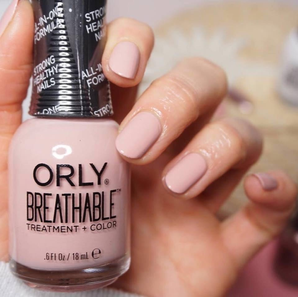 close up on a person holding a ORLY Breathable bottle of nude-like nail polish.