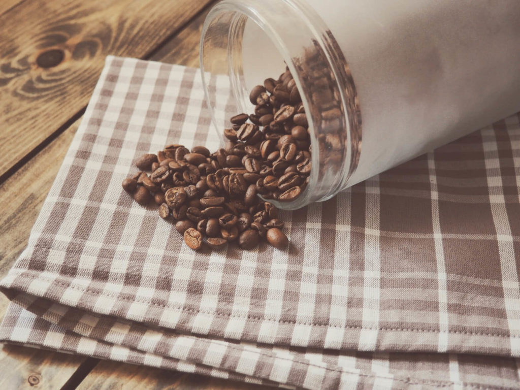 Coffee beans being spilt from a jar onto a towel cloth