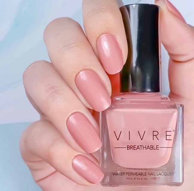 close up of a hand, with delicately painted nails, holding Vivre Breathable Water-Permeable Nail Lacquer.