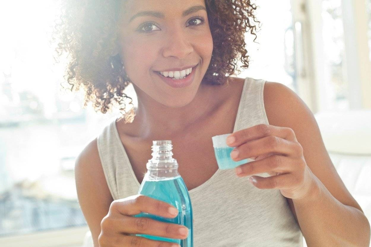 woman holding a capful of mouthwash, smiling.