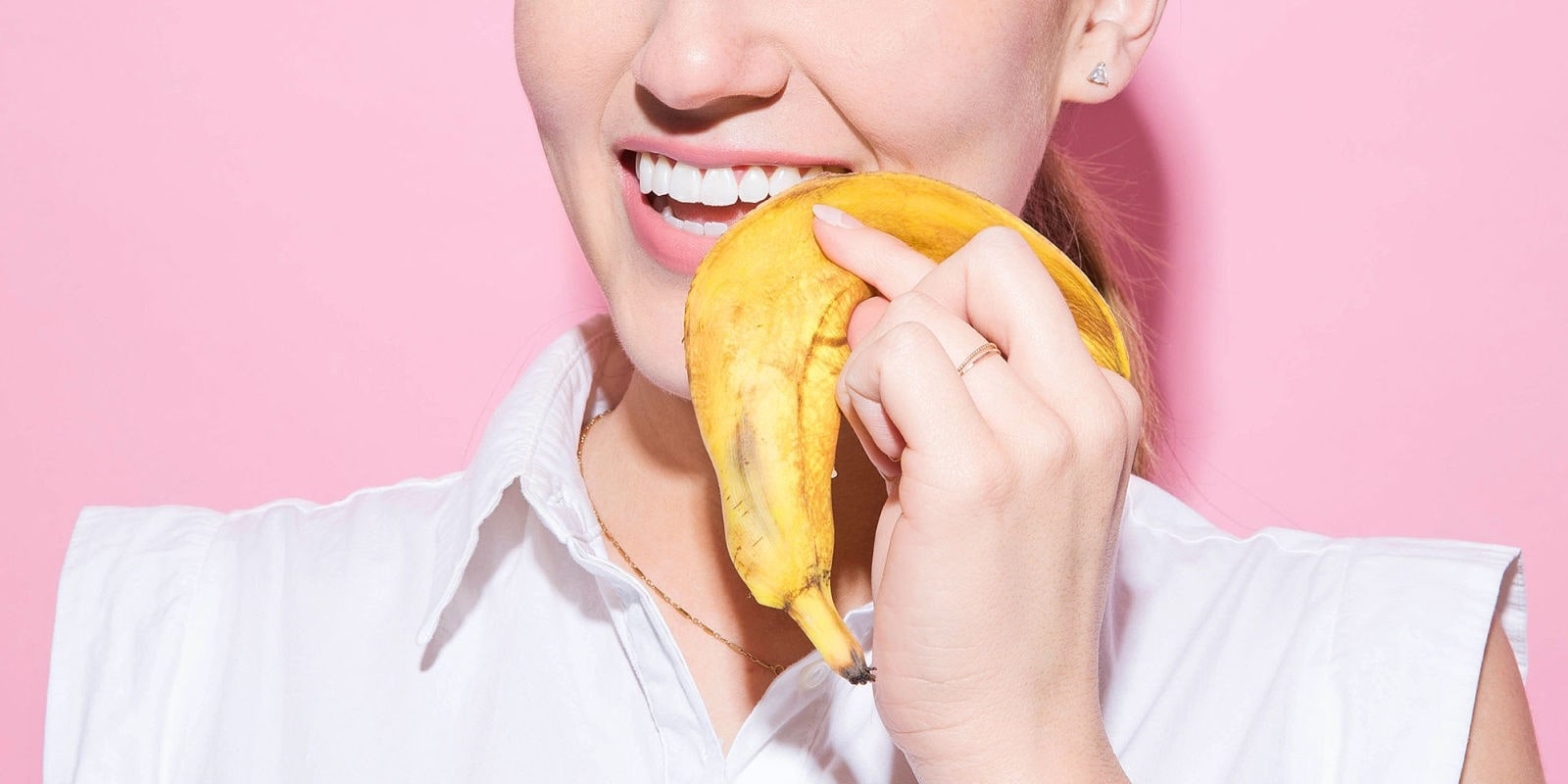 woman using the inside of banana skin on her teeth for teeth whitening purposes.