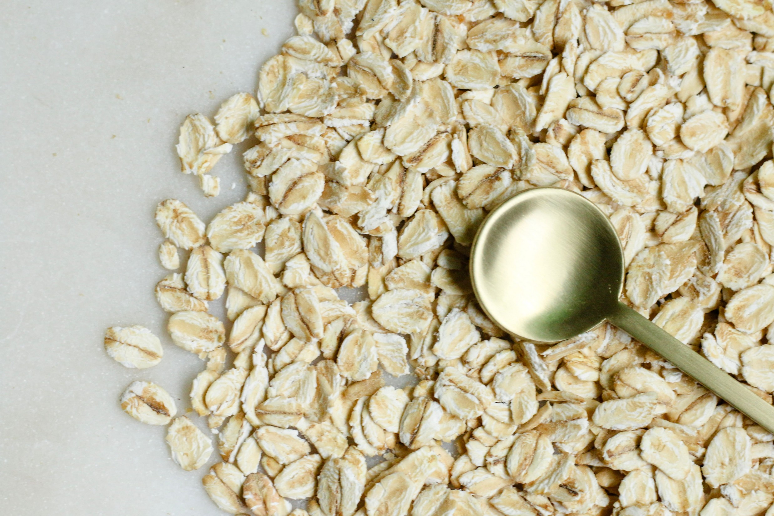 oats on a marble table, with a small golden spoon lay on top.
