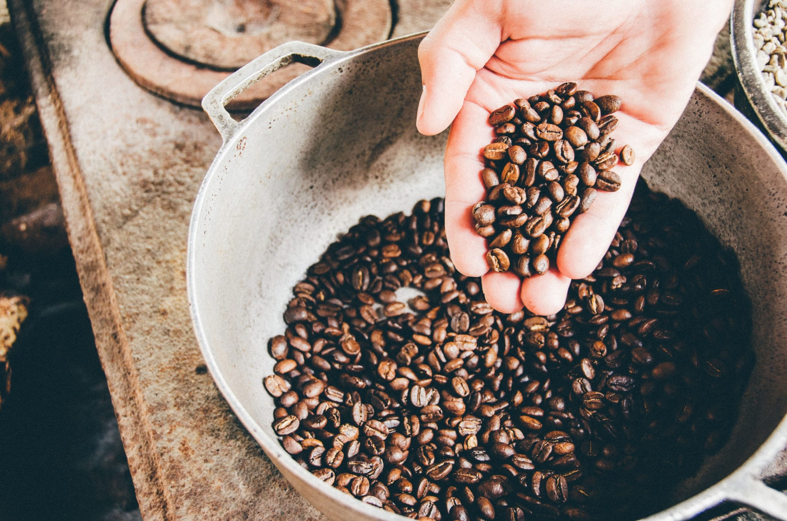 a person holding a handful of coffee beans, pouring them into a bowl below.