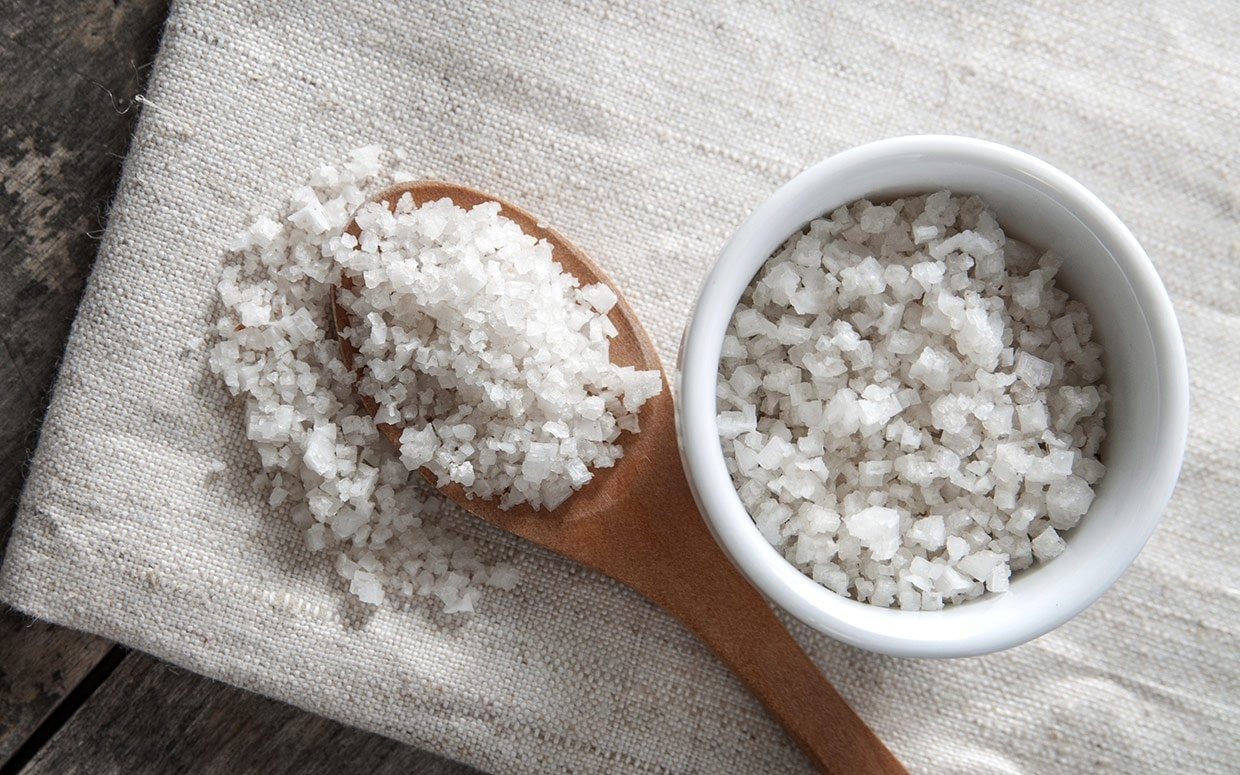 celtic sea salt pictured in a white ramekin and wooden spoon.