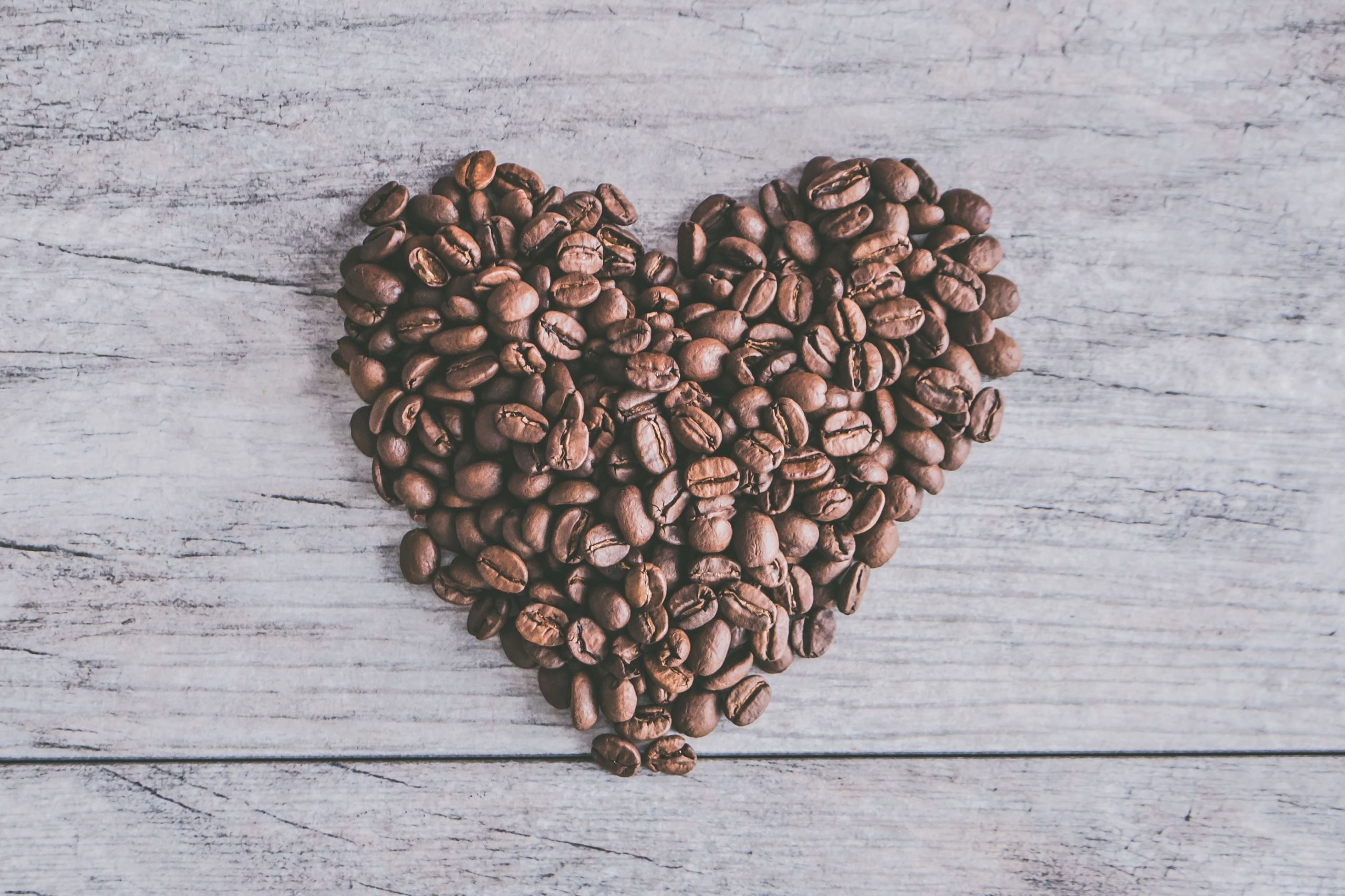 coffee beans shaped into a heart on a wooden background.