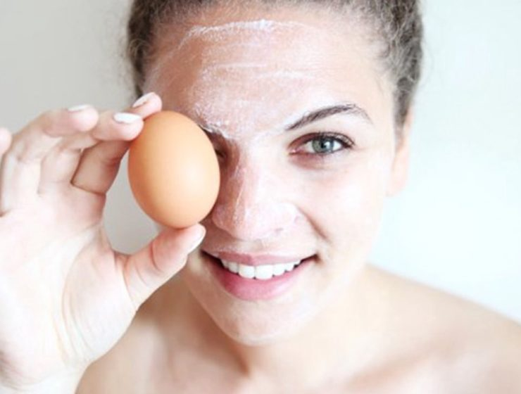 woman wearing egg whites on her face, whilst holding an egg over her right eye, smiling.