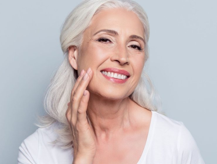 foundations for over 40s: woman smiling, with a finger on her cheek.