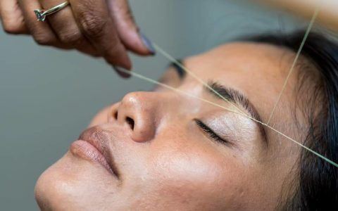 womens having threding on her eyebrows