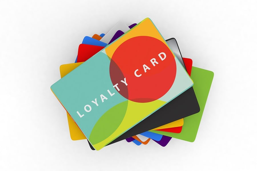 a large pile of credit-type cards with the top card reading 'loyalty card'.