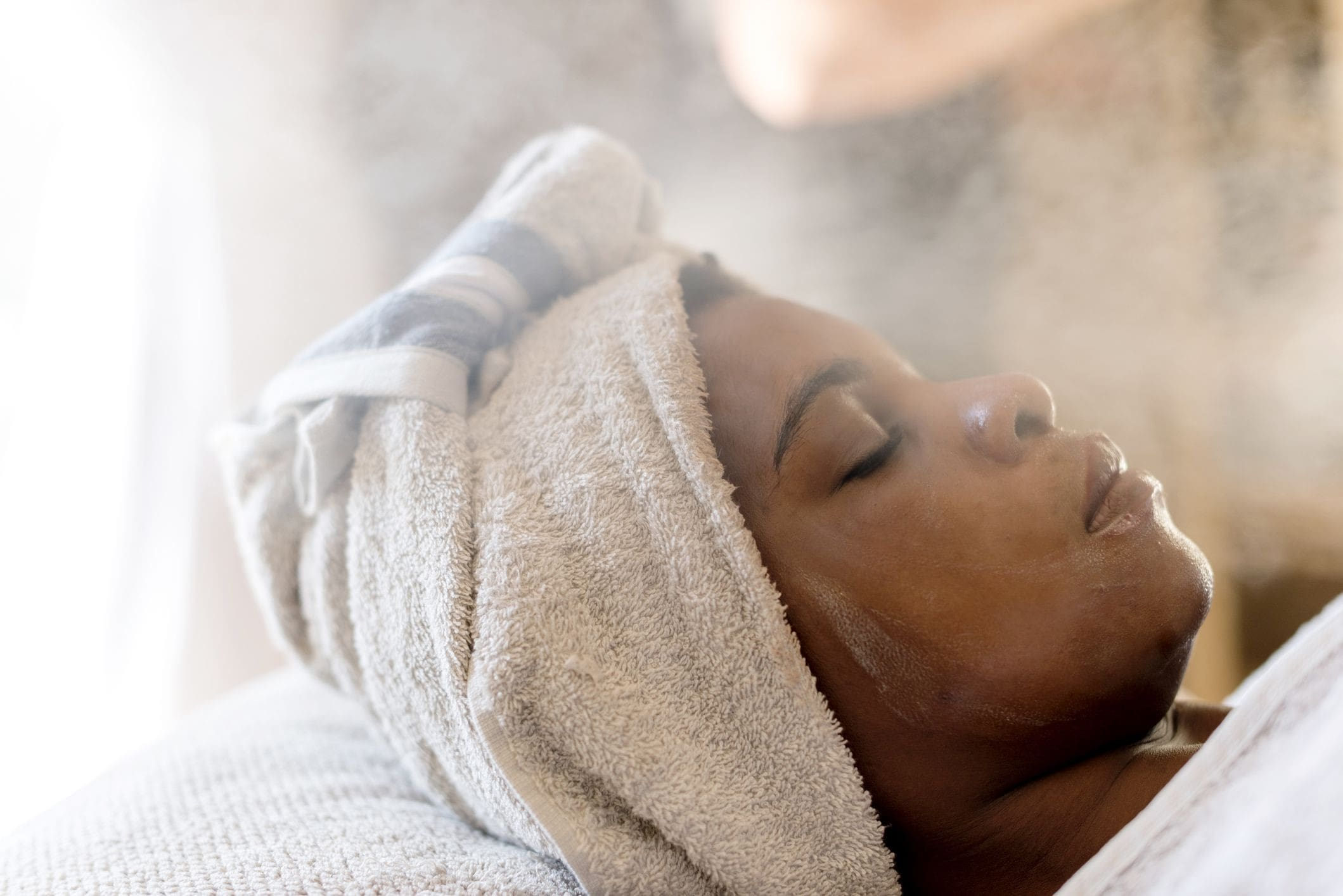 a woman lying in a spa, having a facial steam.