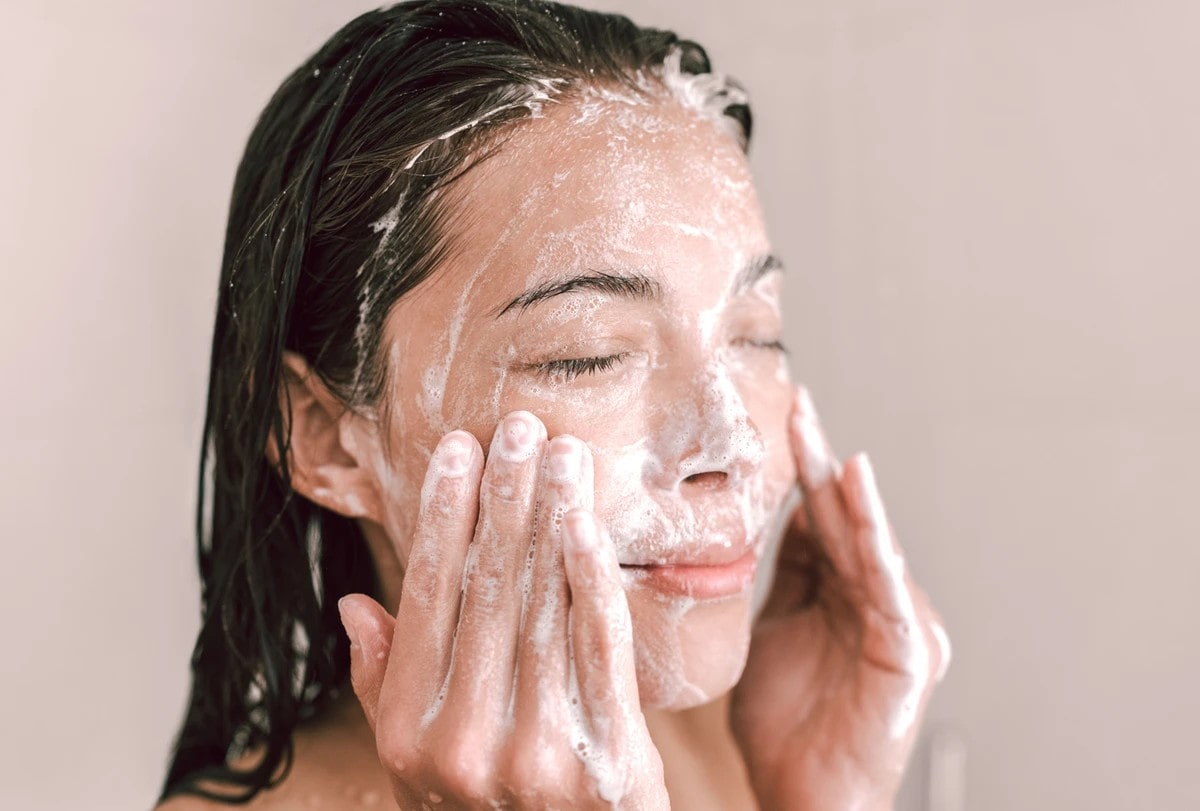 woman exfoliating her face.