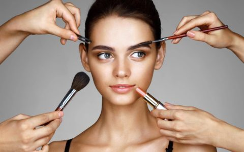 makeup tools being held around a womans' face.