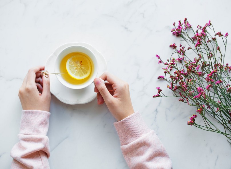 Person holding a cup and saucer, on a table, that has herbal tea with a lemon in it.