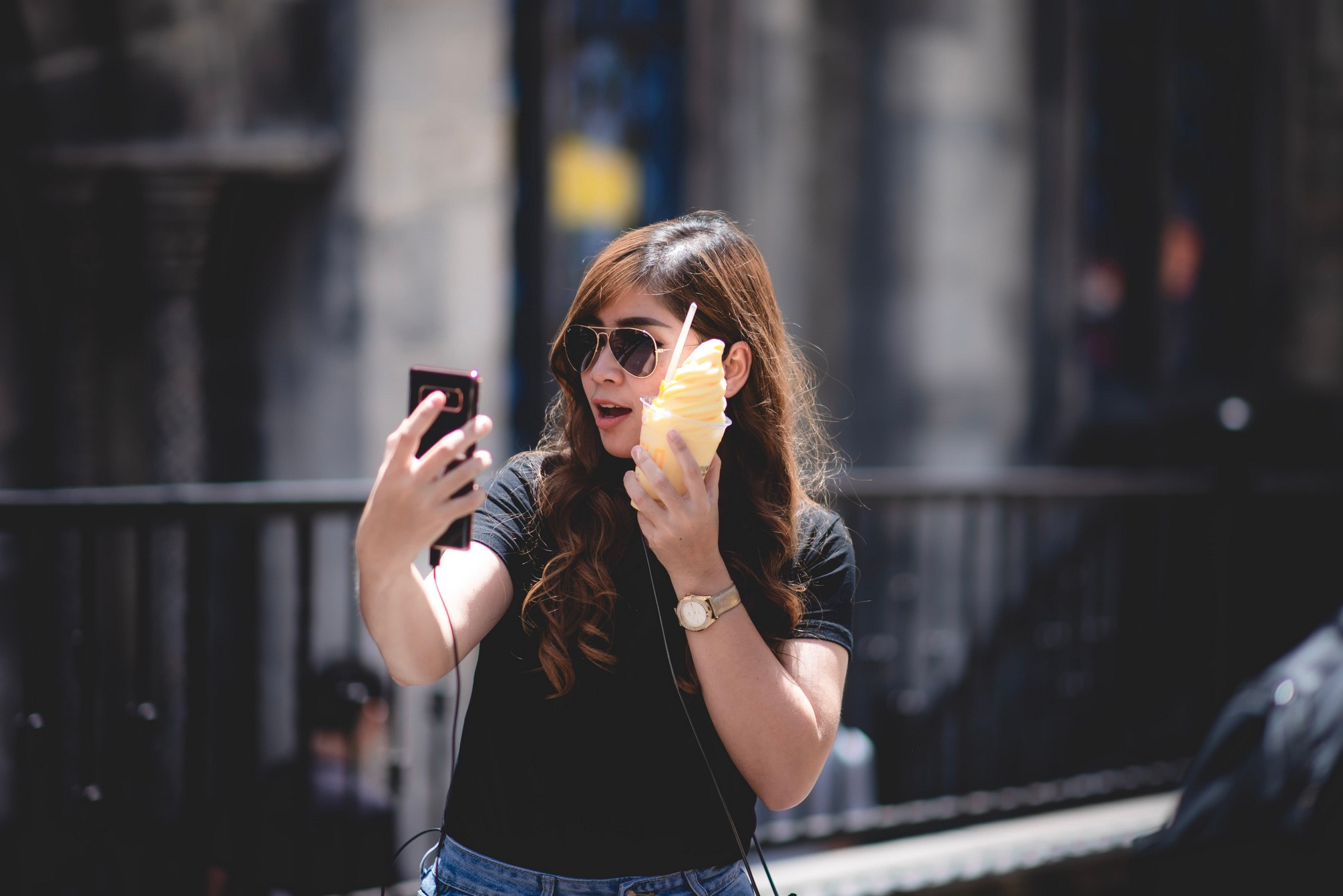 woman looking shocked as she holds her phone in the street.