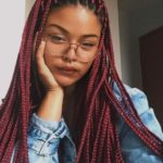 a girl pictured with red coloured box braids.