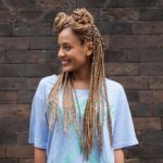 woman smiling with braids, with a wall background.