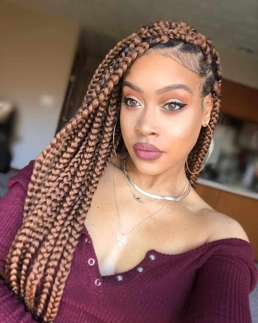 woman wearing her hair in braids and burgandy top.